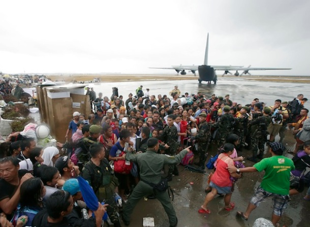 Typhoon survivors rush to get a chance to board a C-130 military transport plane in Tacloban city, Leyte province, central Philippines, Tuesday, Nov. 12, 2013. (AP Photo/Bullit Marquez)