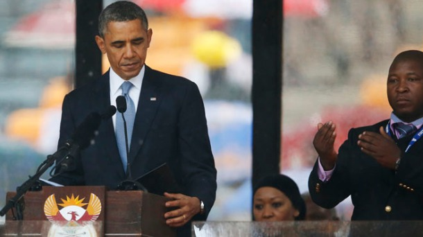 President Barack Obama looks down as he stands next to the sign language interpreter as he makes his speech at the memorial service for former South African president Nelson Mandela at the FNB Stadium in Soweto near Johannesburg, Tuesday, Dec. 10, 2013.  South Africa's deaf federation said on Wednesday that the interpreter on stage for Mandela memorial was a 'fake', (AP Photo/Matt Dunham)